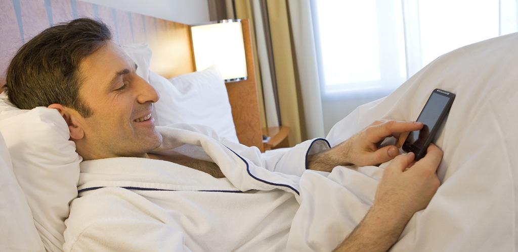 Kaspersky: Mann mit Smartphone im Bett